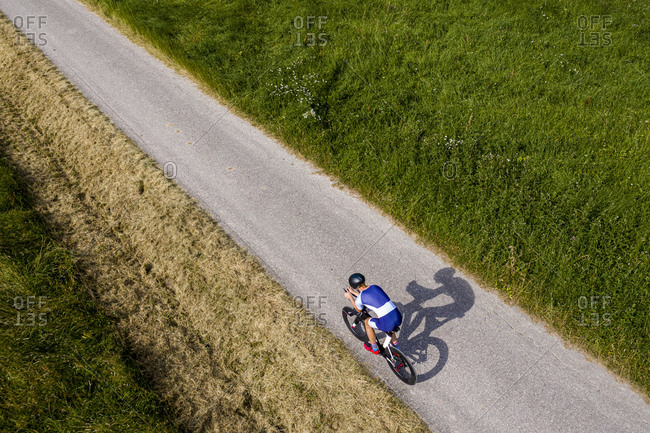Triathlete riding bicycle on country road- Germany