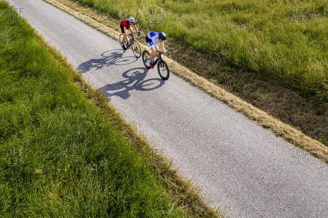 Triathletes riding bicycle on country road- Germany