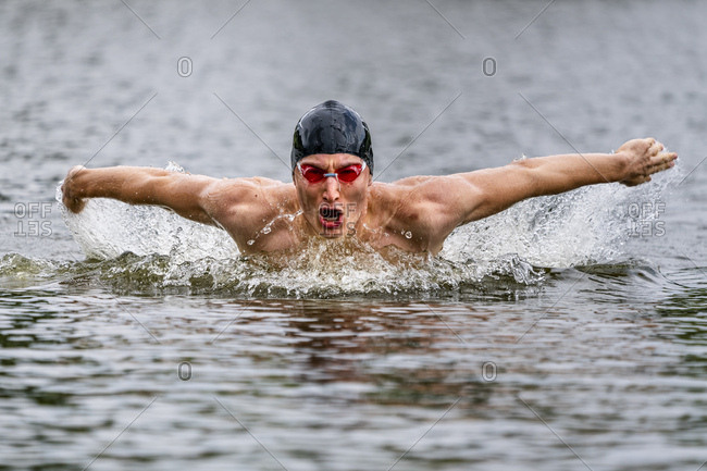 Young triathlete swimming in a lake