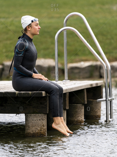Young female triathlete sitting on jetty at a lake