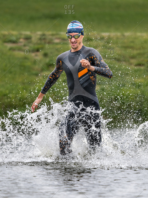 Young triathlete running into a lake