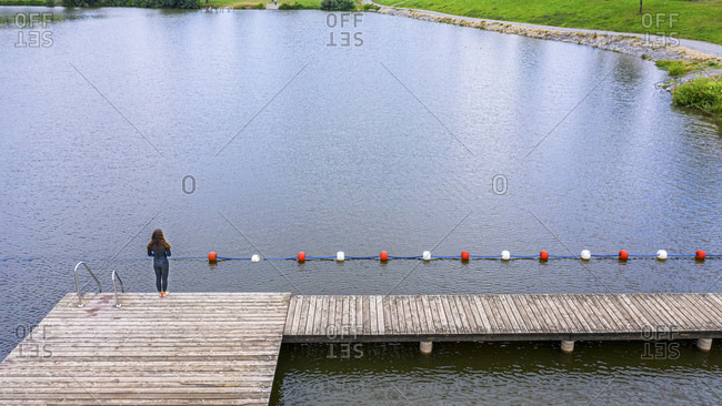 Aerial view of a young female triathlete standing on a jetty at a lake