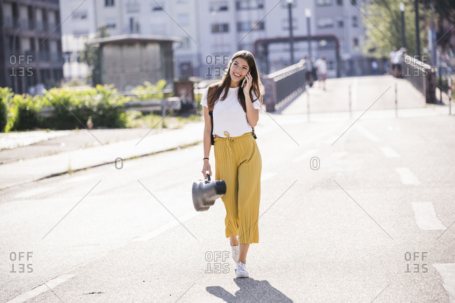 Young woman carrying violin case talking on the phone on the street