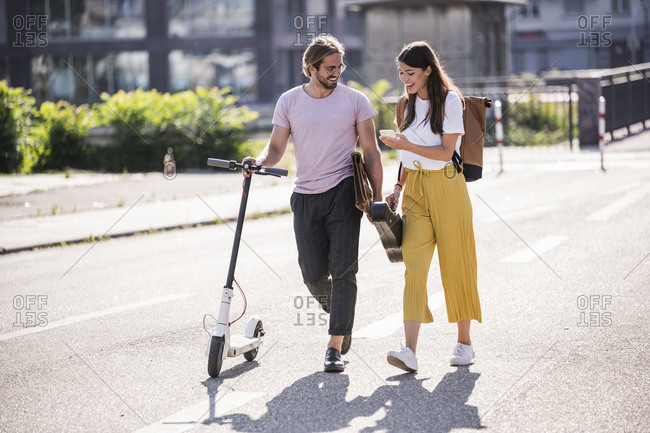 Young couple with electric scooter and smartphone walking on the street