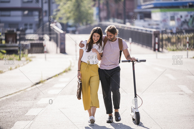 Happy young couple with electric scooter walking on the street