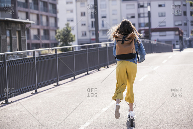 Rear view of young woman riding electric scooter on a bridge