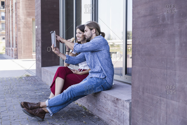Young couple sitting on windowsill at a building using a tablet