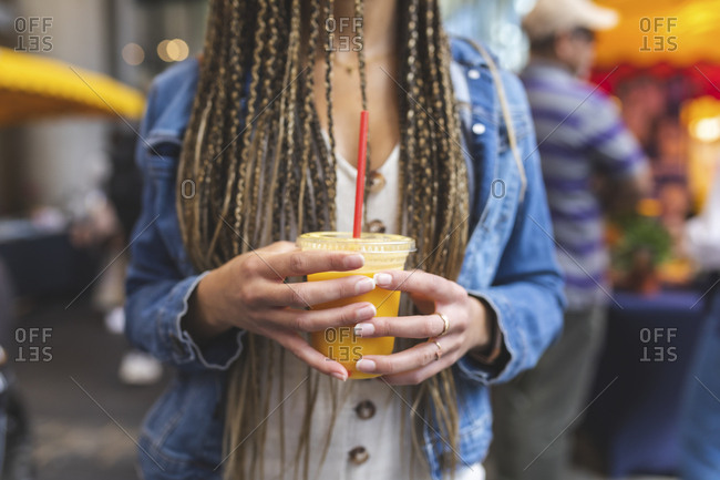 Woman's hands holding plastic cup of fresh orange juice