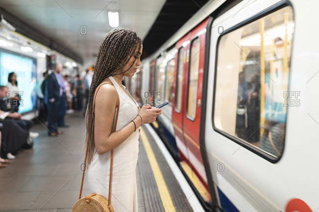 Young woman waiting at subway station platform looking at cell phone- London- UK
