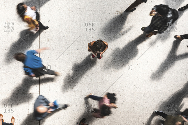 Woman looking at mobile phone in between hurrying people- top view