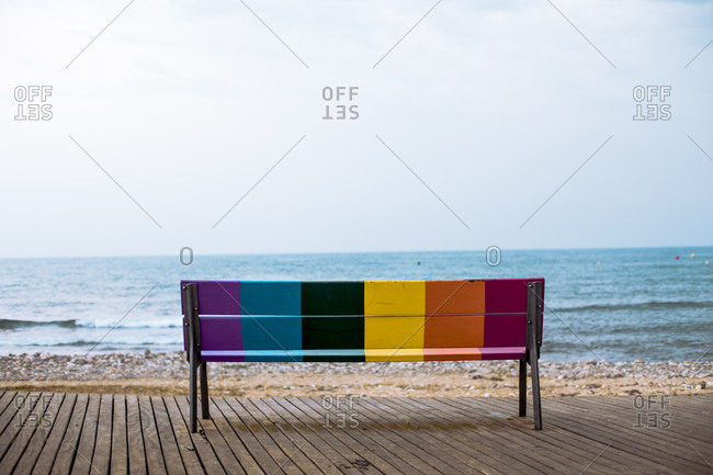 Back view of colorful bench standing in front of the sea- Spain
