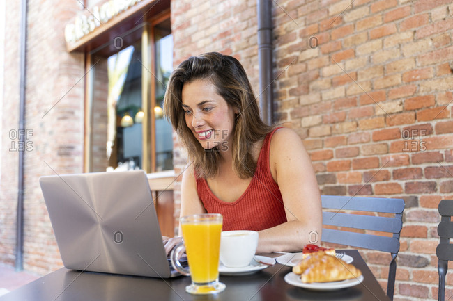 Smiling young blogger sitting at street cafe working on laptop