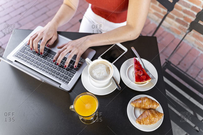 Young blogger sitting at street cafe working on laptop- partial view