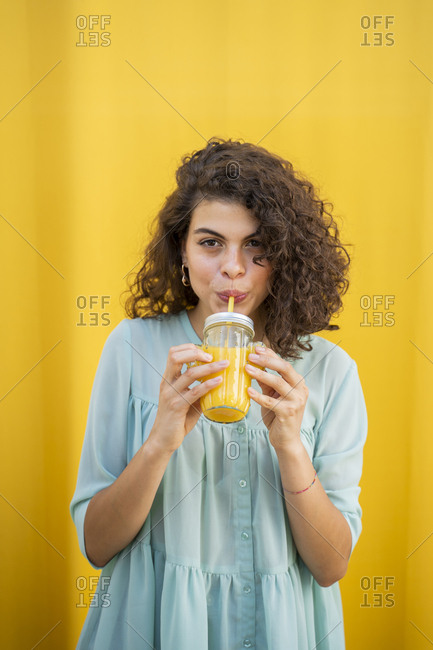 Portrait of woman drinking juice- yellow background