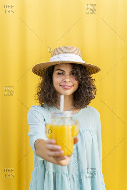 Portrait of woman with straw hat- drinking juice- yellow background
