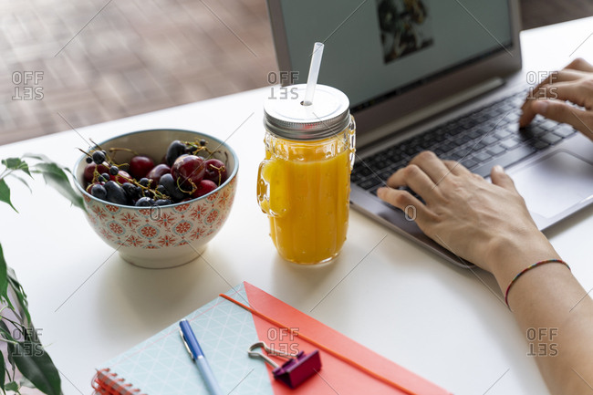 Close-up of woman using laptop at desk with orange juice and fruit