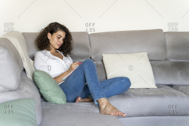 Young woman taking notes on couch at home