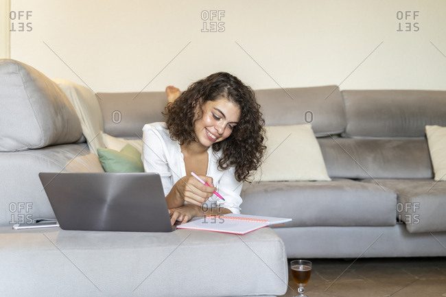 Smiling young woman taking notes and using laptop on couch at home