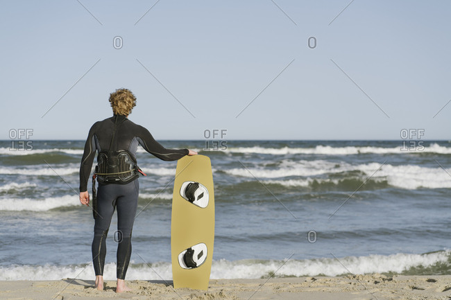 Rear view of kite boarder standing with his surf board at the beach