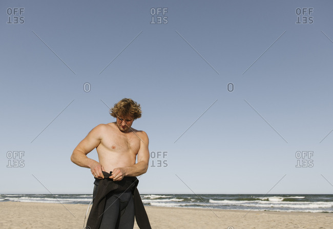 A surfer putting on his wetsuit