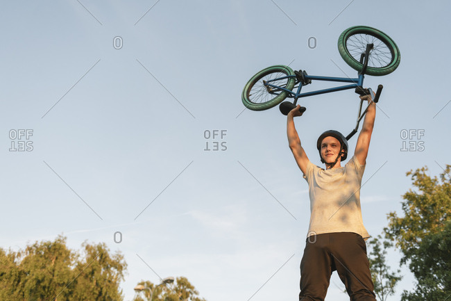 Young man lifting up BMX bike