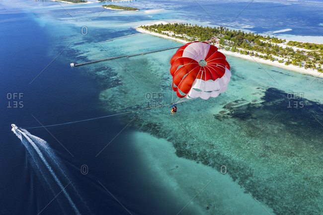 Aerial view of a paraglider flying along an atoll- South Male Atoll- Maldives