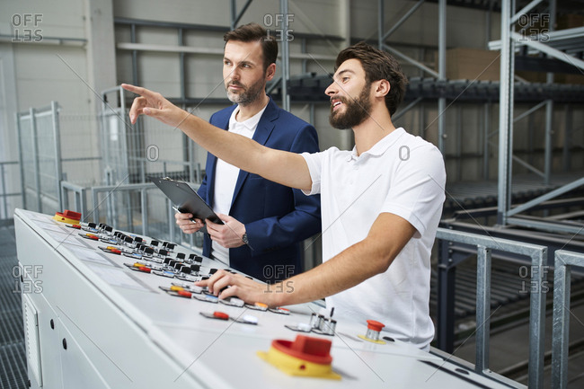 Businessman and employee talking at control panel in a factory