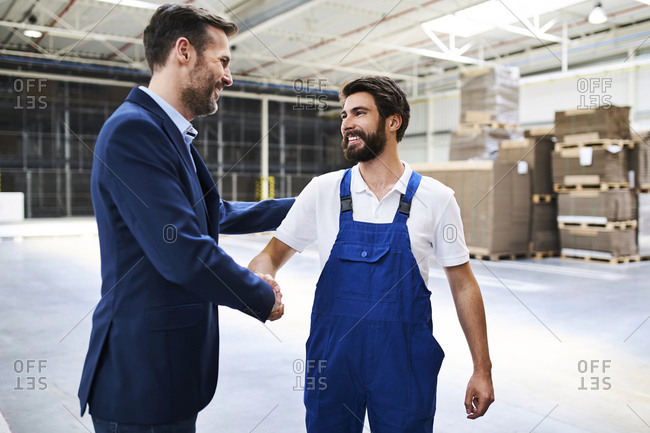 Businessman and worker shaking hands in a factory