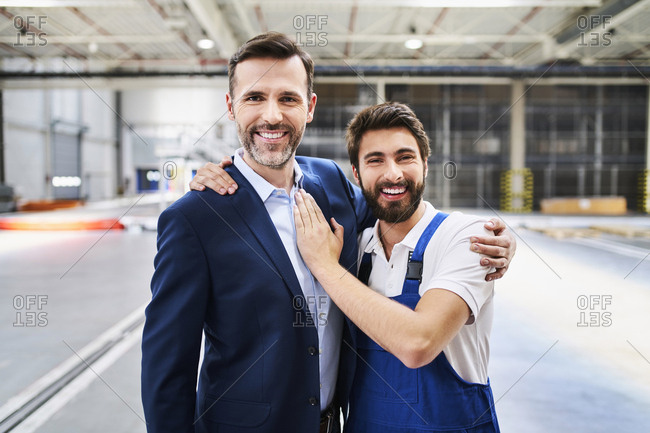 Portrait of happy businessman and worker in a factory