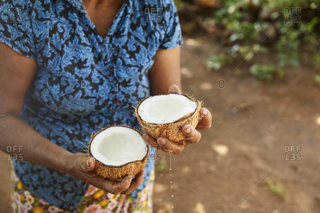 Woman holding two halves of fresh coconut- Sri Lanka