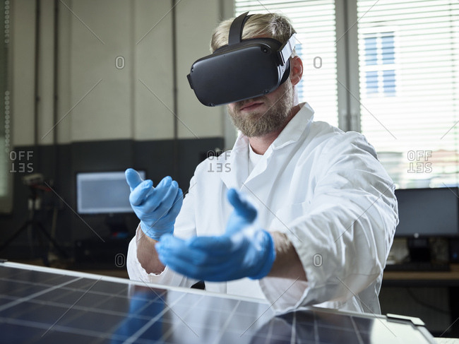 Technician with VR glasses and solar panel in lab