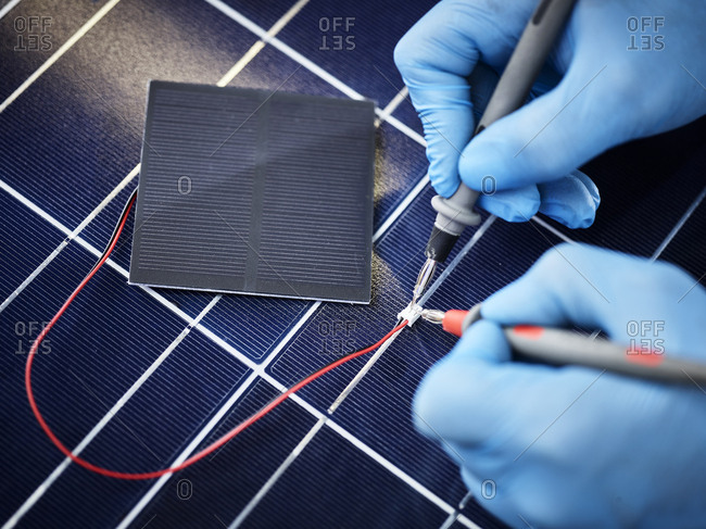 Technician measuring resistor of silicon solar cell
