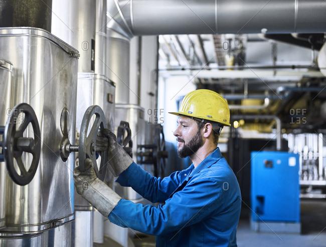 Technician turning a valve