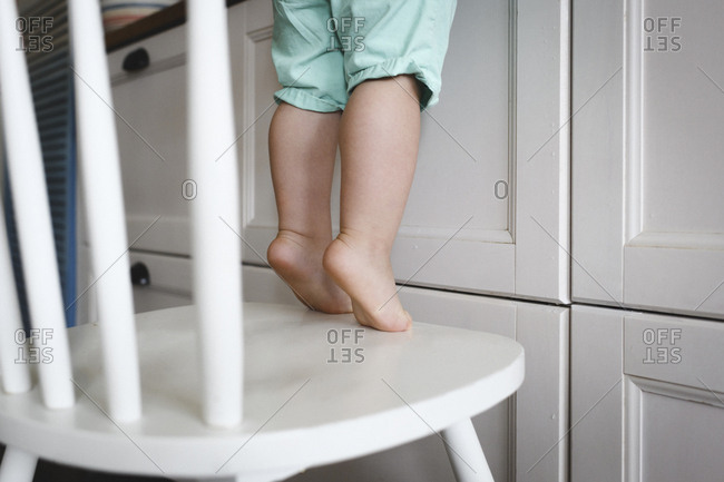 Little boy standing on tiptoes on chair in kitchen