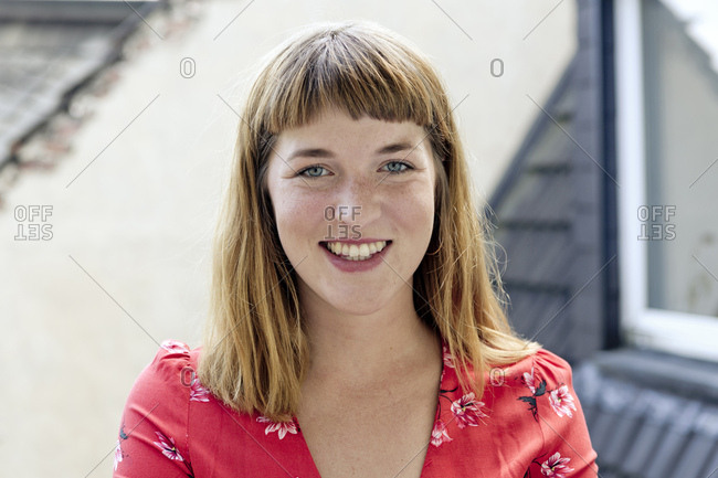 Portrait of smiling young woman with freckles and nose piercing
