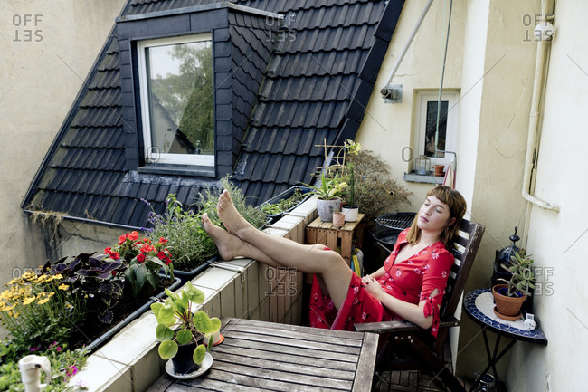 Portrait of pensive young woman relaxing with feet up on balcony
