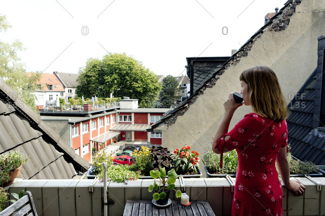 Young woman relaxing with cup of coffee on balcony looking at distance