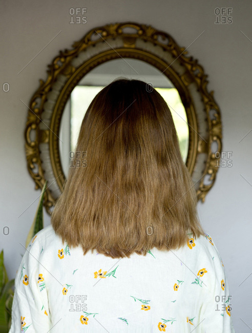 Back view of woman with light brown long hair standing in front of mirror