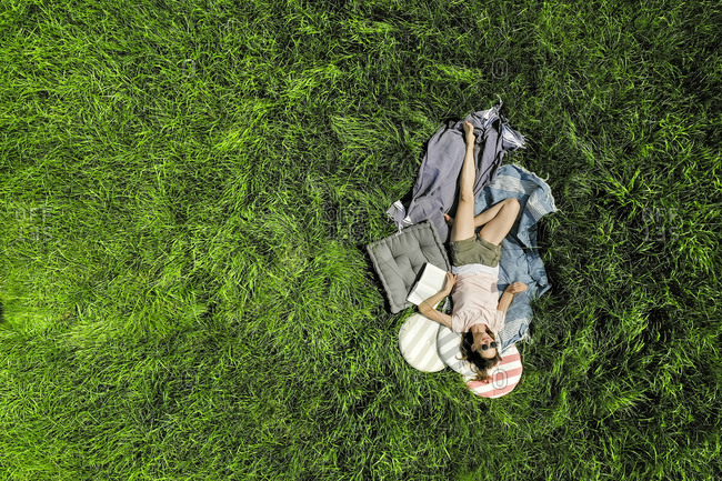 Top view of relaxed woman with book lying on a meadow
