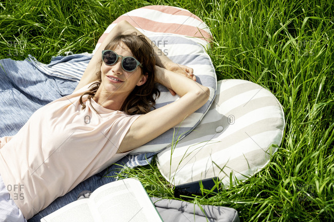 Portrait of smiling relaxed woman lying on a meadow