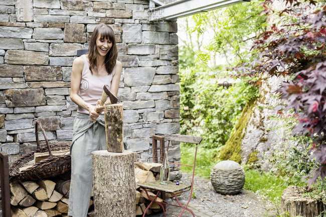 Screaming woman chopping wood in front of a house