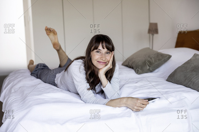 Portrait of relaxed woman lying on bed at home with tablet