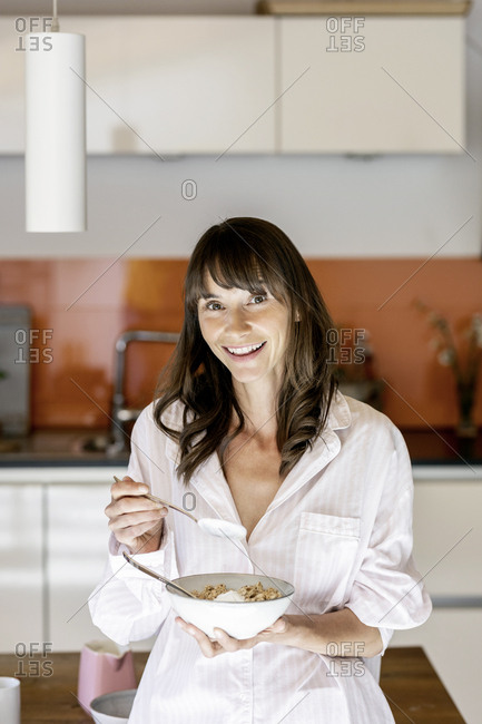 Portrait of woman wearing pajama eating muesli with yogurt in kitchen at home