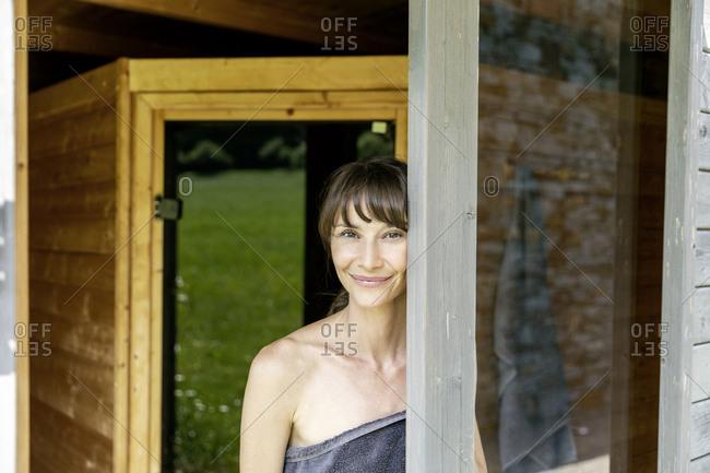 Portrait of smiling woman behind windowpane in a sauna