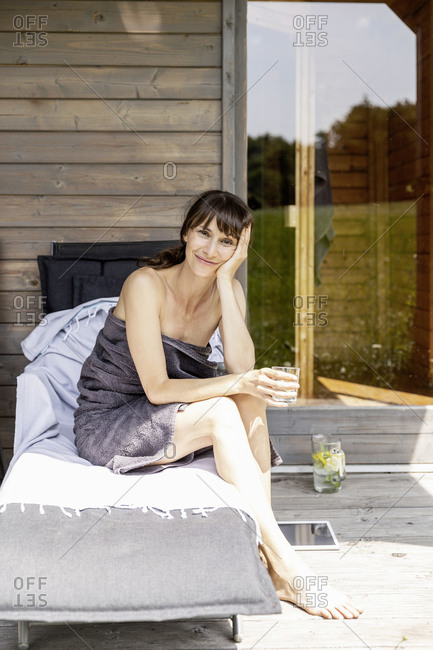 Portrait of woman relaxing on a lounge holding glass of water