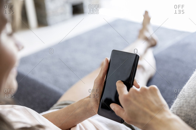 Close-up of relaxed woman using smartphone on couch at home