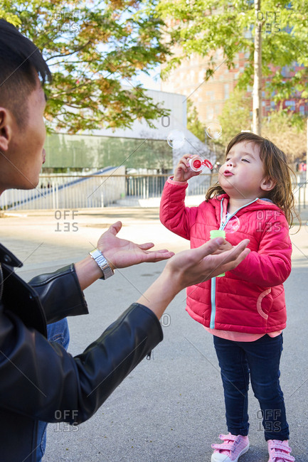 Father and little daughter playing with soap bubbles outdoors