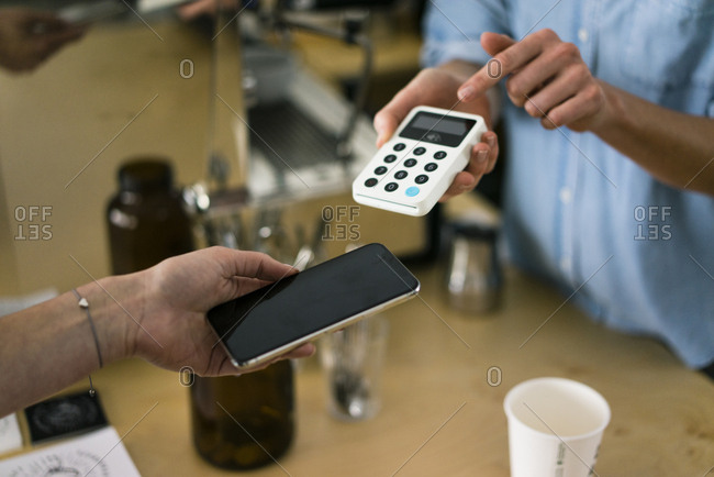 Customer paying contactless in a coffee shop