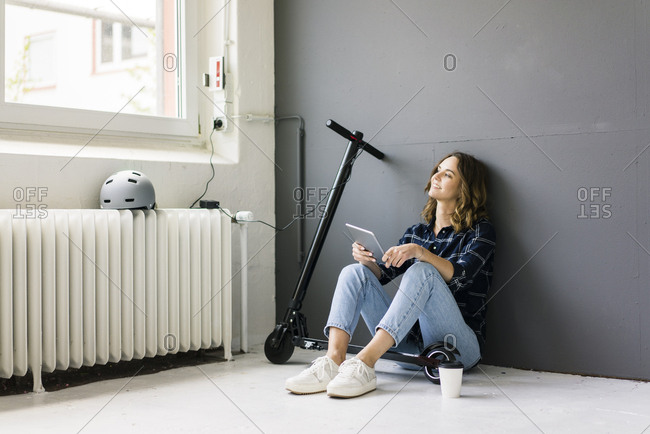 Young woman with e-scooter sitting on floor- using digital tablet