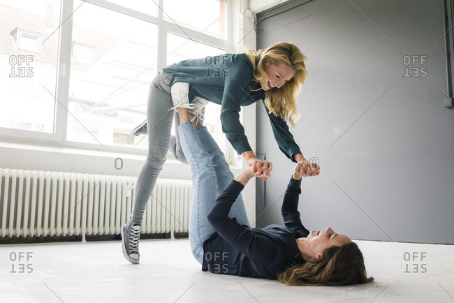 Two young women supporting each other playfully